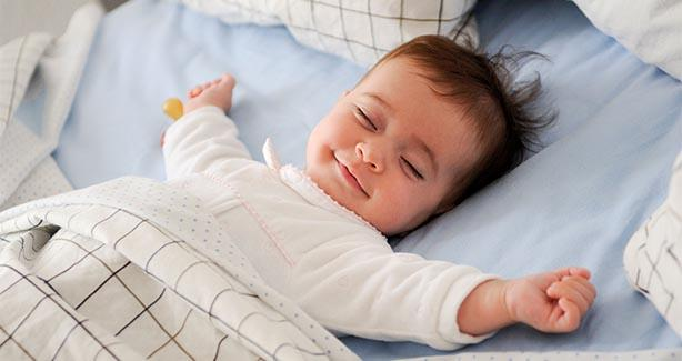 Smiling baby asleep on back